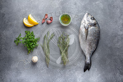 Flat lay with fish dorada or sea bream, herbs, lemon and oil