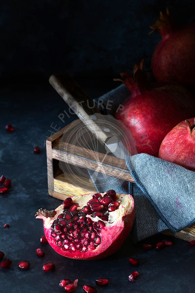 Ripe red pomegranates in wooden box with half a juicy pomegranate in the foreground.