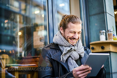 Portrait of laughing young man in front of a cafe looking at tablet