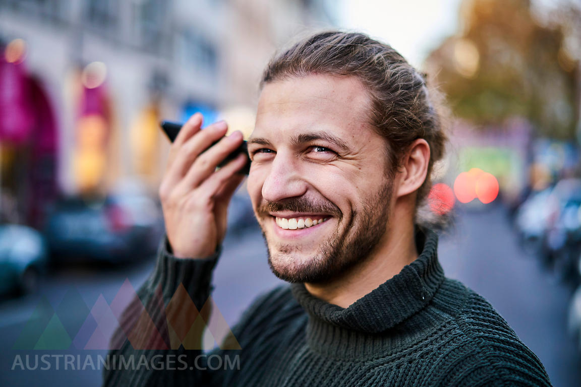 Portrait of laughing young man using smartphone on the street in the evening