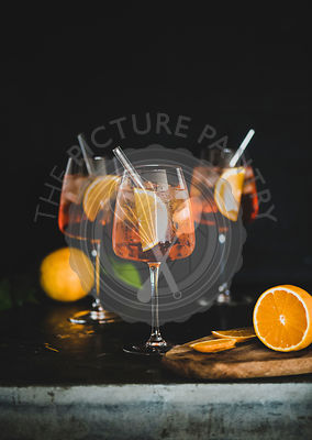 Aperol Spritz cocktail in glass with oranges, black background