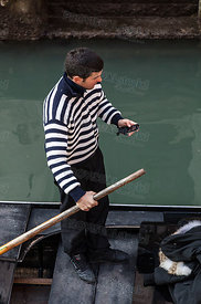 Gondolier Checking his Mobile Phone
