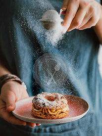Woman sprinkles icing sugar on Choux Paris Brest pastry with hazelnut