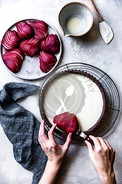 Hands placing a sliced poached pear onto the filling of a custart tart with a chocolate crust.