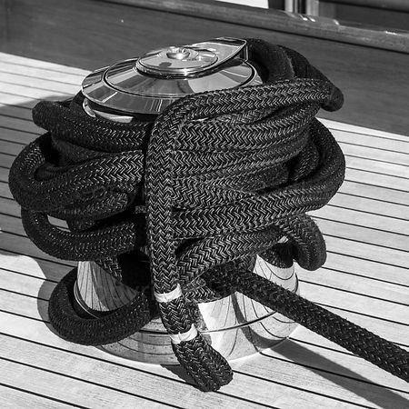 Abstract wall art of winch and black rope on a classic yacht