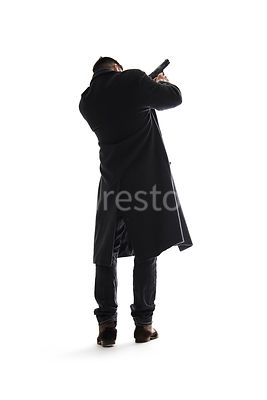A silhouette of a mystery man in a long black winter coat, pointing a gun – shot from low level.