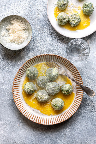 Spinach ricotta gnudi on a plate.