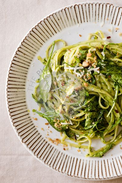 Creamy pesto pasta with spinach, Parmesan cheese, and crushed red pepper on a plate.
