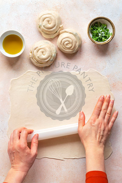 Preparing scallion pancakes.Hands rolling the dough.