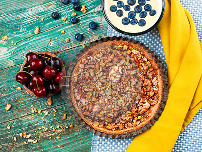 Homemade walnut tart with cherry jam, cherries, blueberries, vanilla curd on a wooden table, top view