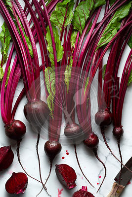 Washed baby beetroots on a marble tile surface. A knife with beetroot juice and a cut beetroots are alongside.