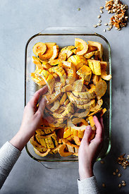 Hands placing pieces of delicata squash in a pan for roasting.