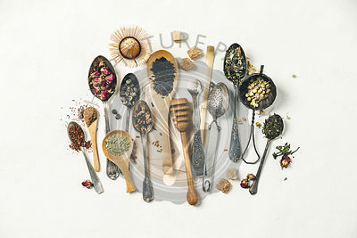 Creative composition with Various kinds of dry tea, silver and bamboo spoons and sugar on white wintage canvas background