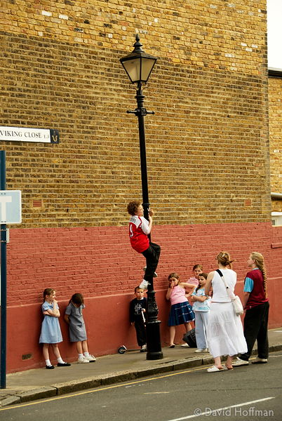Children in Tower Hamlets using a street light as a climbing frame.