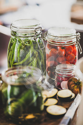 Ingredients and jars with homemade vegetables preserves on table