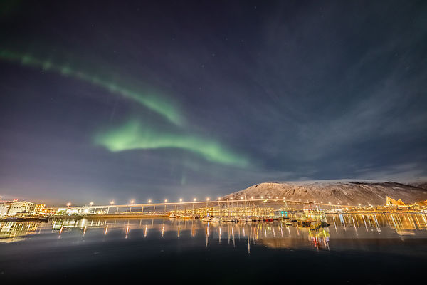 The northern lights dance above the Tromsø Bridge and the Arctic Cathedral