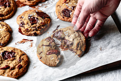 Closeup view of a hand breaking a chocolate chip cookie in half.