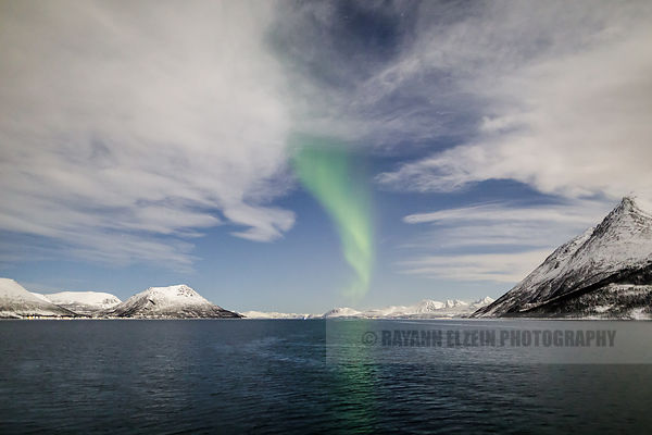 The nothern lights (aurora borealis) make a brief appearance between clouds in a fjord near Tromso, Norway