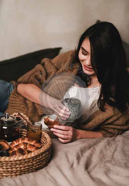 Young smiling brunette woman having breakfast in bed