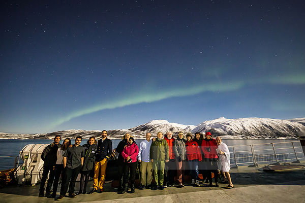 A group of tourists and part of the crew of the Polarfront under the Aurora Borealis near Tromso, Norway