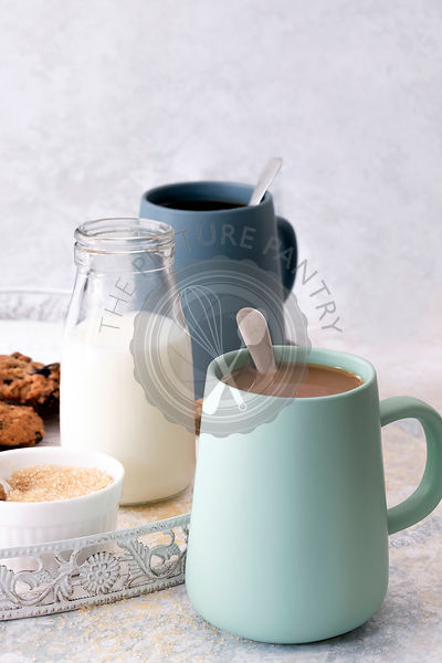 Mugs of white and black coffee with date cookies.