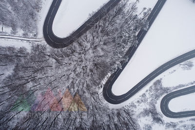 Austria, Wienerwald, winding road in snow-covered landscape, aerial view