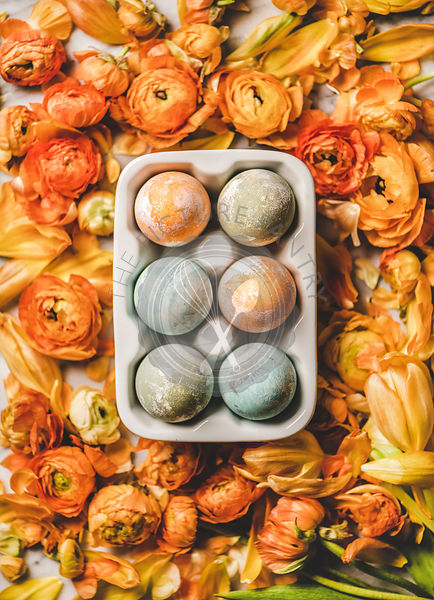 Flat-lay of colorful dyed Easter eggs over blooming orange flowers