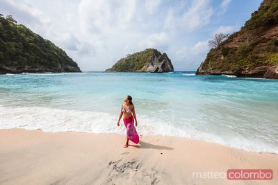 Asian woman walking at Atuh beach, Nusa Penida, Bali