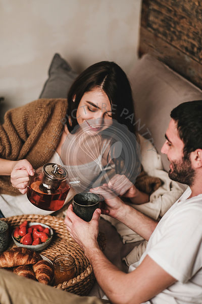 Happy couple having breakfast with croissants and tea in bed