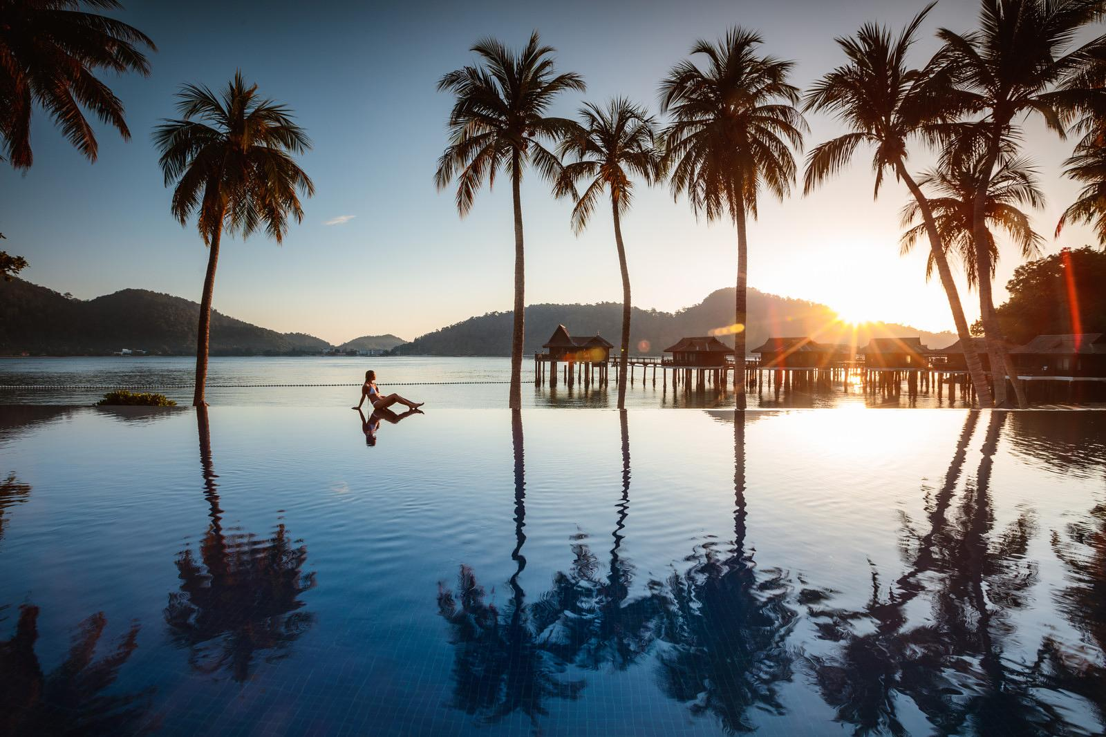 Woman enjoying sunrise in a luxury resort