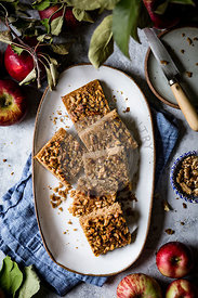 An apple snack cake cut into squares placed on an oval plate.
