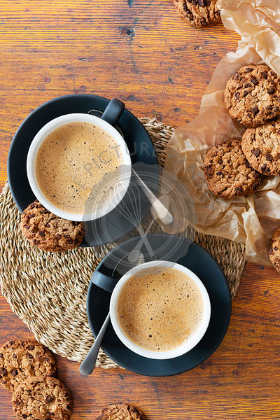 Cups of cappuccinno coffee with chocolate chip cookies on baking paper.