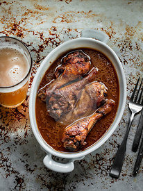 Marinated baked chicken drumstick in thai pepper sauce in baking dish with beer in tall glass on the side