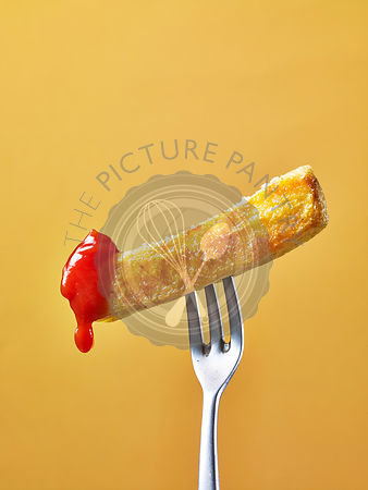 A chip dipped in tomato sauce on a fork against a yellow background