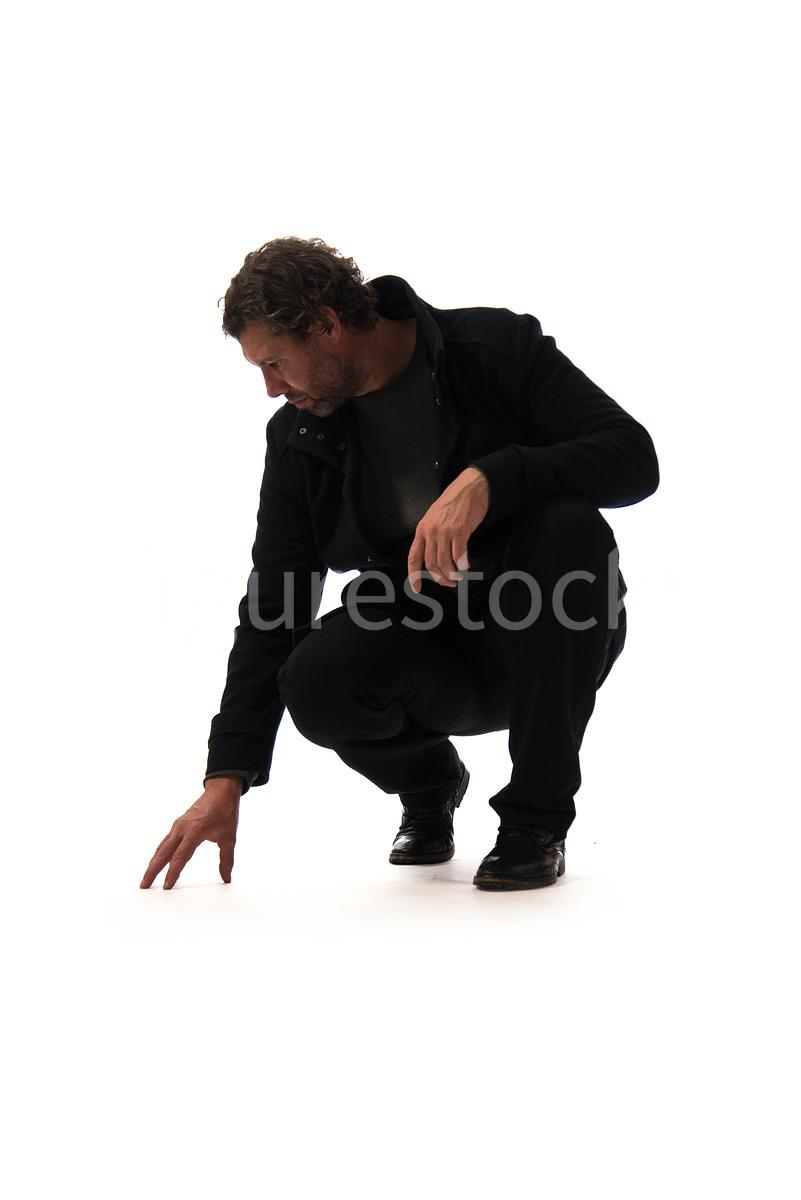 A crouching mystery man, looking down, in semi-silhouette – shot from low level.