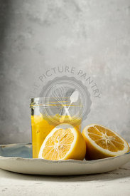 Fresh lemons,  sliced in half, arranged on a blue hand made plate, with a spoon in a jar of home made lemon curd.