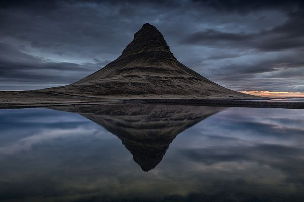 The Kirkjufell mountain reflected in the water of Grundarfjordur bay at sunrise, Snaefellsnes Peninsula, in western Iceland.