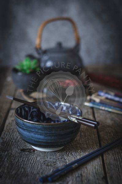 Chopsticks and meal in a rustic kitchen .