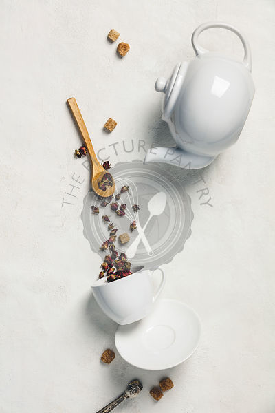 Making herbal tea concept. Dry rose buds pouring into cup on white canvas surface.