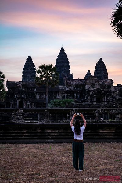 Woman taking a picture of Angkor Wat at sunrise