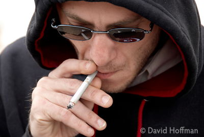 Teenager in a hoodie smokjing a cigarette.