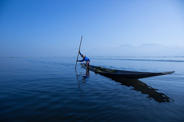 Fisherman in Longtail Boat at Twilight