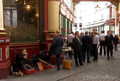 Shoe shiners among the office workers strolling through the upmarket shops in Leadenhall market, London.