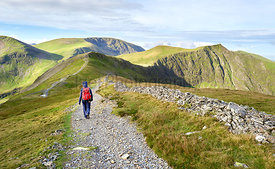A hiker walking along a stone chip path on a mountain ridge towards the summits of Hobcarton and Hopegill Head in the Lake Di...