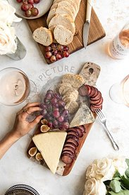Fall cheeseboard with hand in frame and rose.