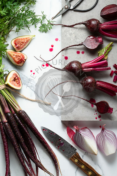 Baby beetroots, purple carrots, purple onions and figs, being sliced and prepared on a marble tile surface. A knife, scissors...