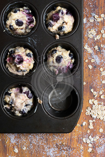 Mixed berry and oat muffin batter in a muffin pan.