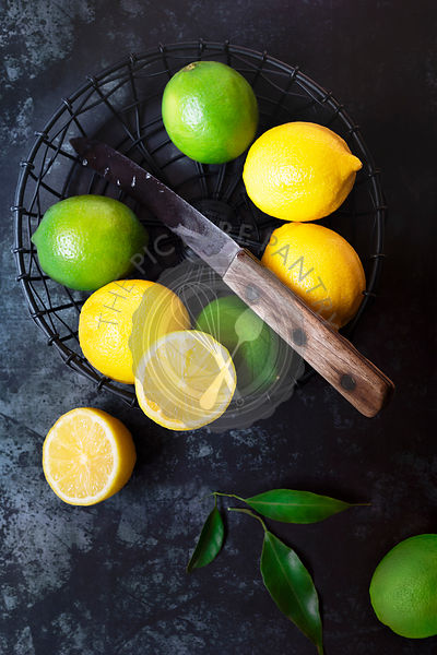Lemons and limes in a wire basket.