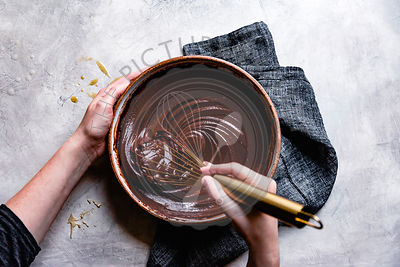 Chocolate ganache mixed in a bowl by a hand held whik.