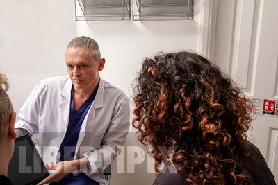A genderqueer doctor and two patients looking at a computer screen in a clinic-LGBTQ+ stock photos